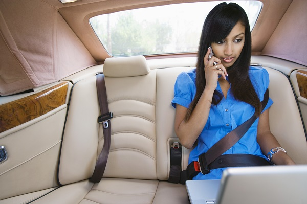 Young Woman Talking on Phone and Using Laptop in Car